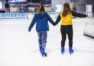 Two young girls ice skating