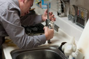A plumber fixing a sink.